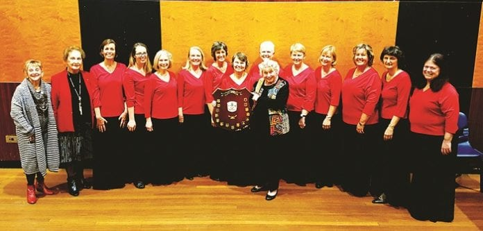 The Carlson Chorale pictured after the Ryde Eisteddfod win. L-R Adjudicator Pamela Herring, Ryde Eisteddfod Chairman Edna Wilde OAM, Sarah Woolley, Kathryn Jenkins, Lesley Wilson, Marilyn Murray, Jenny Holmes, Carole Handley, Beth Treseder, Rosalind Carlson (with shield), Julie Watts, Corinne Lodewijks, Rhys Kitto, Rosanne Jackson, Elizabeth Willis.